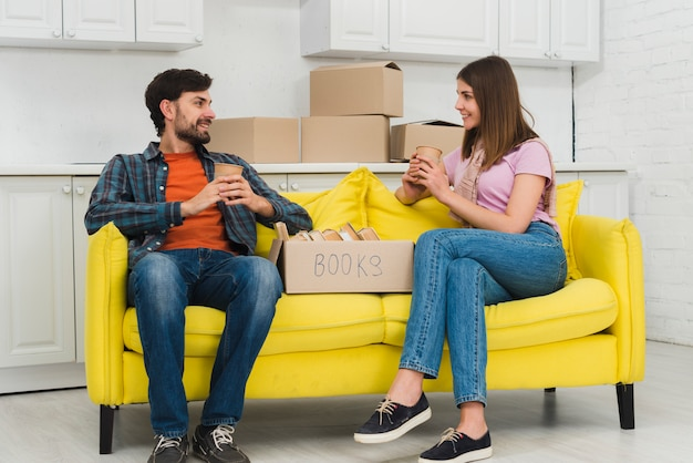 リビングルームの段ボール箱を手にコーヒーカップを保持している黄色いソファーに座っていた若いカップル