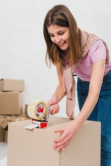 Улыбается молодая женщина, держа упаковочную машину и запечатывания картонных коробок с клейкой лентой