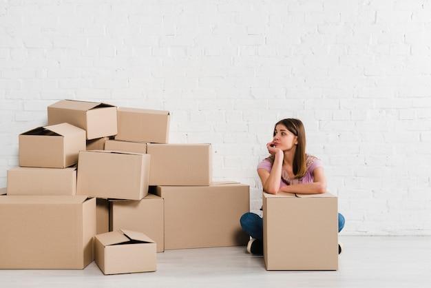 Подавленная молодая женщина, глядя на картонные коробки