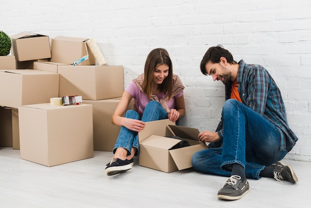 若いカップルが彼らの新しい家で段ボール箱を開く