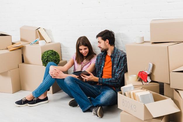 段ボール箱の山の間に座っている彼女の妻に男を示すデジタルタブレット