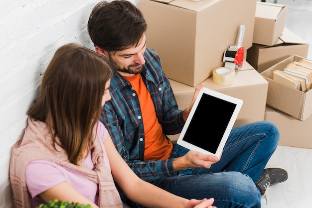 デジタルタブレットを示す彼女の夫を見ている若い女性