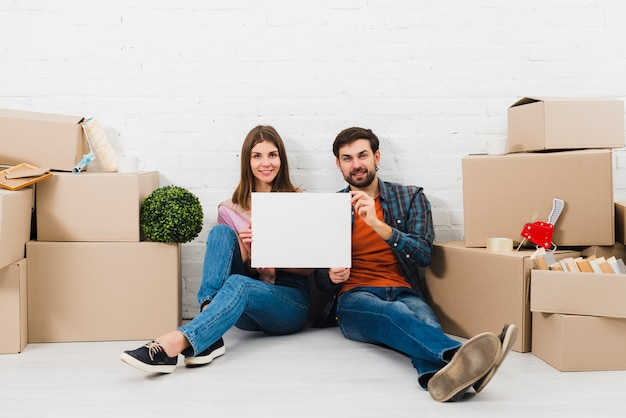 段ボール箱の間に座って空白の白いプラカードを示す若いカップルの笑顔