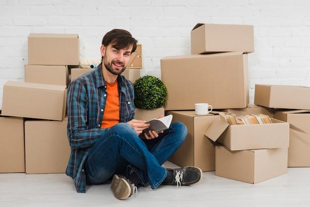 Портрет улыбающегося молодого человека, сидя перед картонные коробки, глядя в камеру