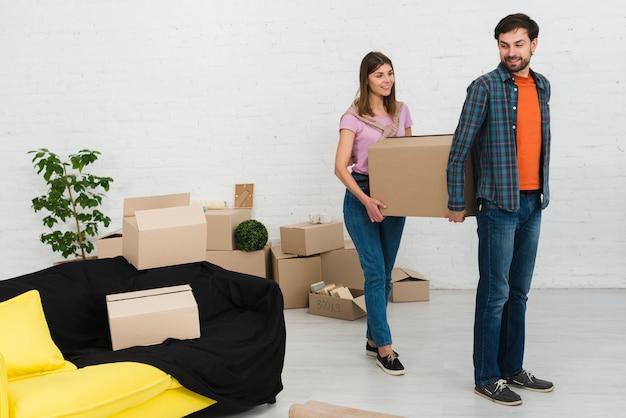 Молодая пара держит картонную коробку в новом доме