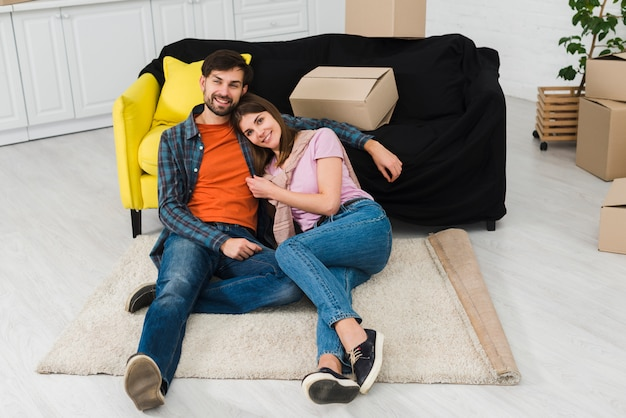 Молодая пара отдыхает на ковре возле дивана нового дома