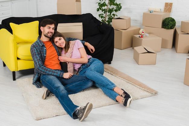 Улыбающаяся молодая пара отдыхает в своей новой квартире