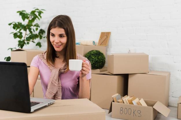 Портрет молодой женщины, держащей чашку кофе в руке, используя ноутбук в своем новом доме