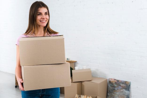 Веселая молодая женщина держит картонные коробки в своем новом доме