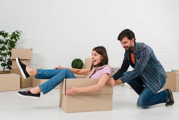 段ボール箱に座っている彼の妻を押す夫