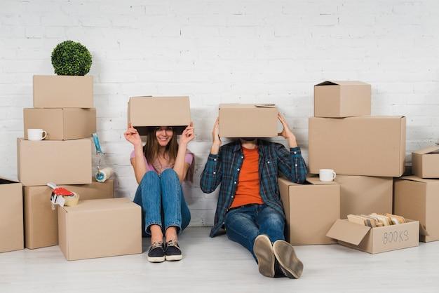 若いカップルが彼らの新しい家の段ボール箱の間に座って彼らの顔を隠して