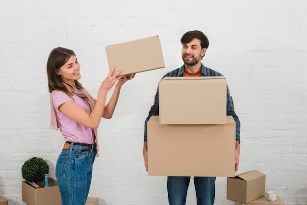 Улыбающаяся женщина кладет стопку картонных коробок на руку мужа