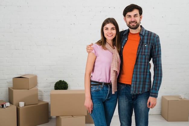 彼らの新しい家で段ボール箱を持つ若いカップルの肖像画を笑顔