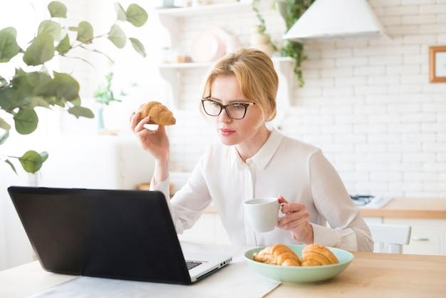 Вдумчивый бизнес женщина, используя ноутбук во время еды круассан