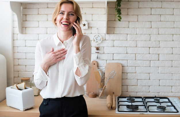 Деловая женщина разговаривает по телефону на кухне