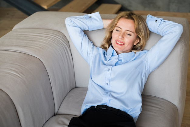 金髪のビジネス女性がソファに横になっています。