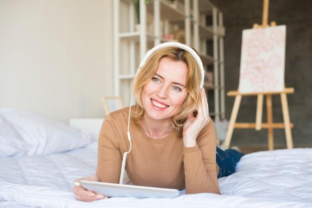 Женщина в наушниках слушает музыку на кровати
