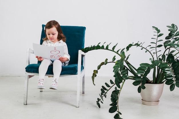 Маленькая девочка читает открытку с надписью «я люблю маму»
