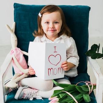 Девушка держит открытку с надписью я люблю маму