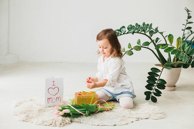Девочка сидит с подарочной коробкой и цветами тюльпана