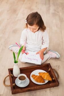 Девушка пишет счастливый день матери возле подноса с кофе
