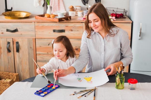母と娘の紙に絵を描く