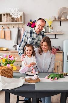 台所でカップケーキを作る両親と娘