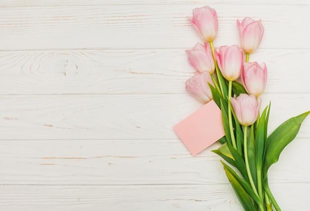 木製のテーブルの上に空のカードとチューリップの花束