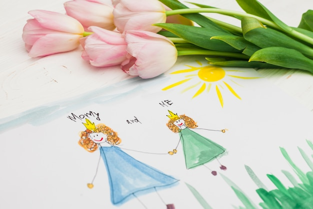 子供と母親の描画とテーブルの上の花