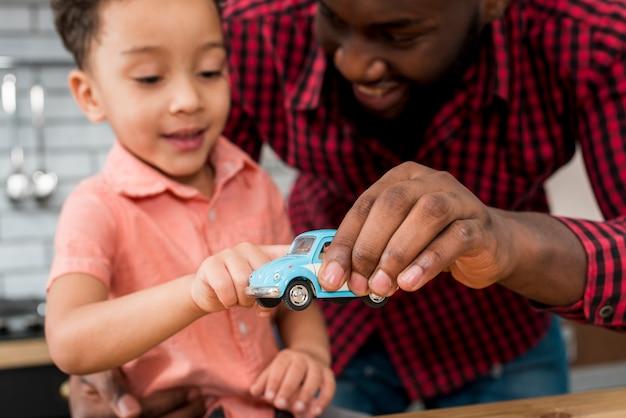 黒の父と息子のおもちゃの車で遊ぶ
