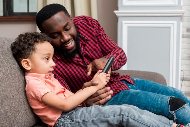 Черный отец и сын, используя смартфон на диване