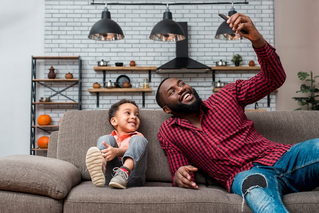 Черный счастливый отец и сын, принимая селфи