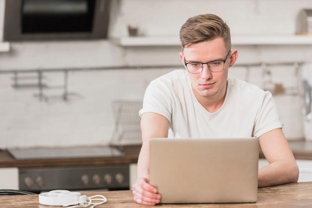 Портрет молодой красавец, глядя на ноутбук