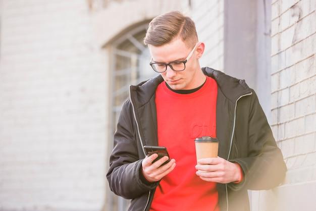 若い男が手に使い捨てのコーヒーカップを保持している携帯電話を見て