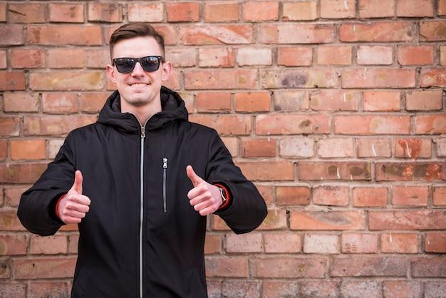 レンガの壁に立っているサインを親指を示す笑みを浮かべて若い男の肖像