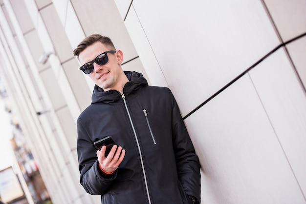 スタイリッシュな若い男が手に携帯電話を保持している壁にもたれて