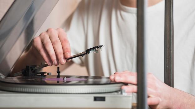 男性の手のクローズアップはレトロなビニールレコードプレーヤーを設定します