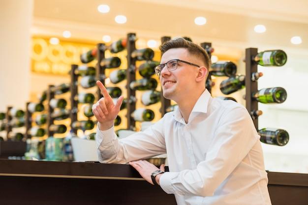 Улыбающийся молодой человек сидит возле барной стойки, указывая пальцем