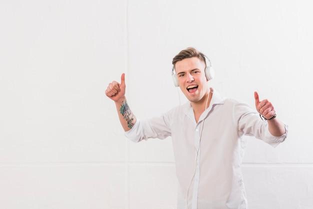 Молодой человек, наслаждаясь музыкой на наушники, показывая большой палец вверх знак против белой стене