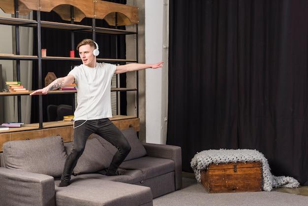 若い男が自宅のソファーで踊っているヘッドフォンで音楽を聴く