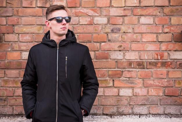 レンガの壁の前に立っているポケットに手を持つ魅力的な若い男