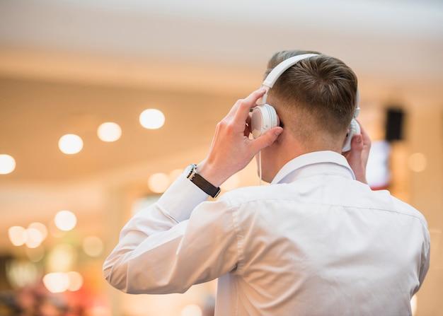 白いヘッドフォンで音楽を聴く若い男の背面図