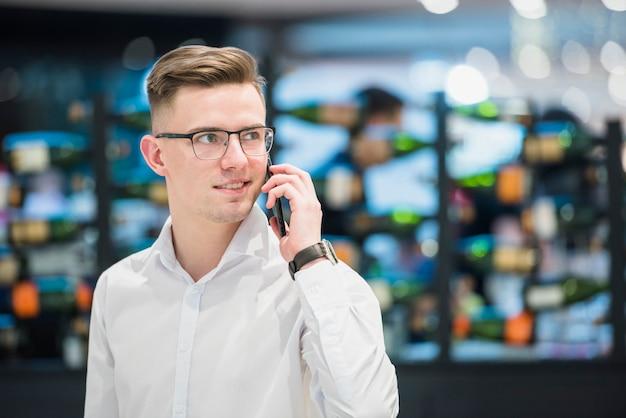 Портрет счастливого уверенно молодого бизнесмена стоя в баре говоря на мобильном телефоне