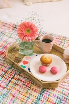 ガーベラの花とマカロンとトレイの上のコーヒー