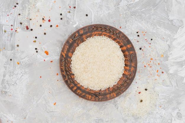 Возвышенный вид рисовых зерен на тарелке в окружении красного и черного перца на бетонном фоне