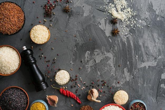 Сырье и различные сорта риса, расположенные на шероховатой бетонной поверхности