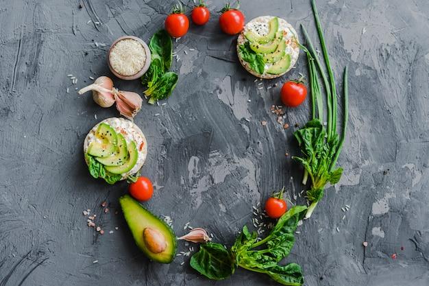 織り目加工の表面上の新鮮な野菜で作られた円形のフレームのオーバーヘッドビュー