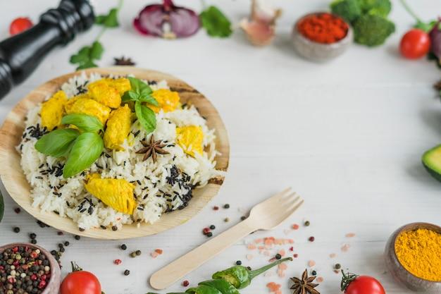 Вкусная еда в круглой тарелке со специями и овощами на белой поверхности