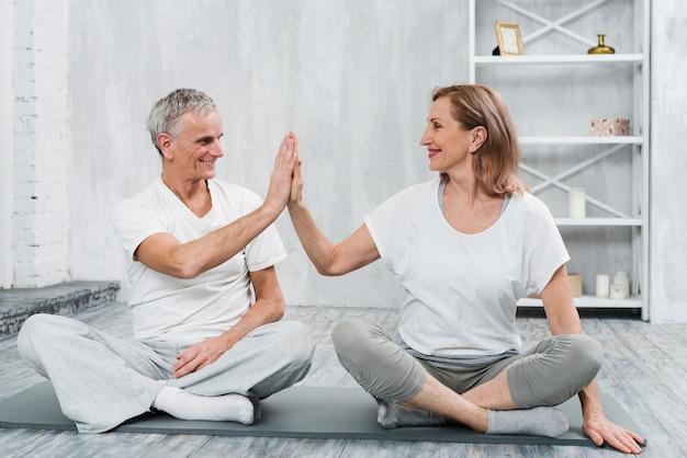 陽気な年配のカップルがマットの上で一緒に運動しながらハイファイブを与える