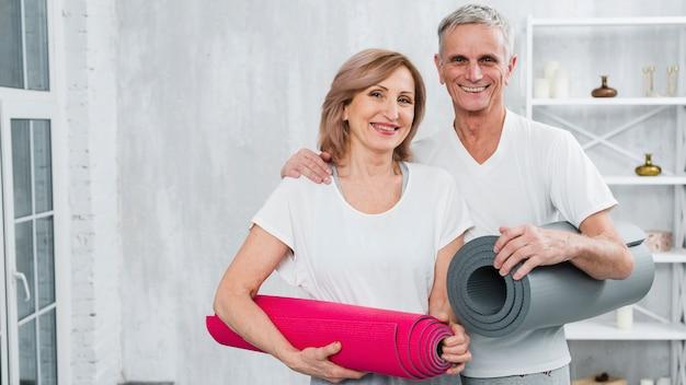 ヨガマットを運ぶスポーツウエアで笑顔の年配のカップルの肖像画